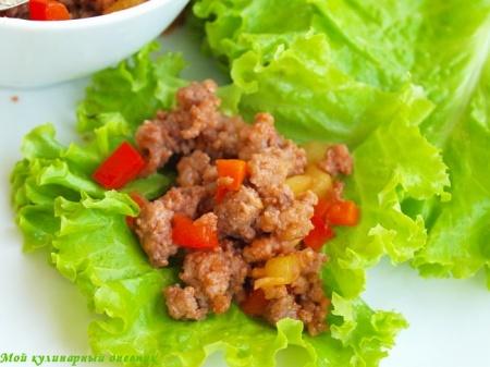 Молотая свинина с овощами на листьях салата