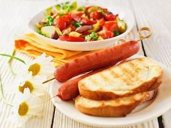 Теплый овощной салат и сосиски на гриле